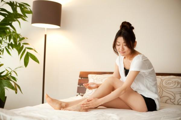 ベッドの上で脚をマッサージする女性