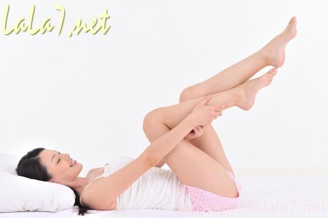 ベッドで脚をマッサージする女性