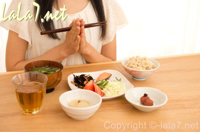 和食を目の前にしている女性 いただきますと手を合わせている