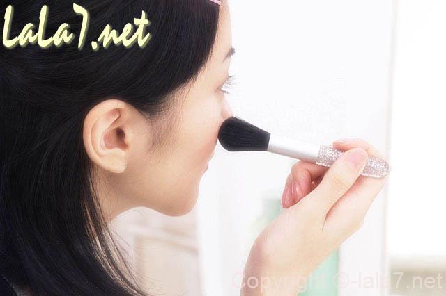 鏡に向かって化粧 チークをつけている女性
