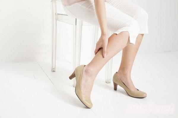 椅子に座りふくらはぎに手をあてている女性 白い服 パンプス
