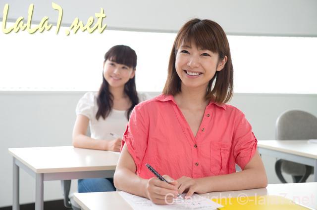 机に座り話に耳を傾けている女性二人 微笑んでいる