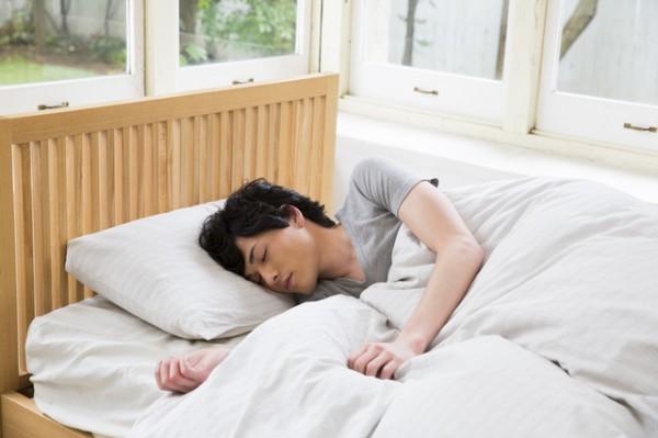 ベッドで眠っている若い男性