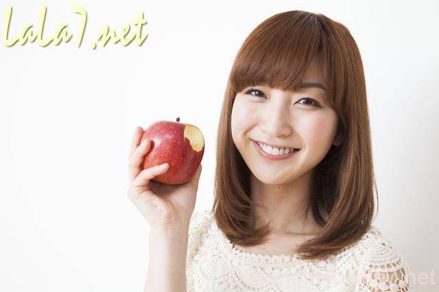 若い女性 微笑んでりんごをかじる