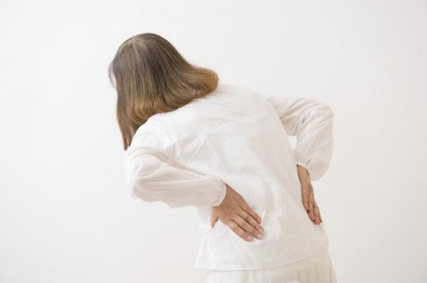 腰痛で腰をかばう女性後むき