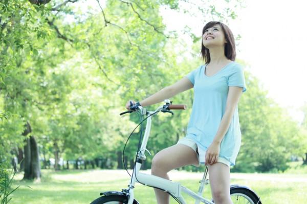屋外で自転車に乗る若い女性空をみあげている