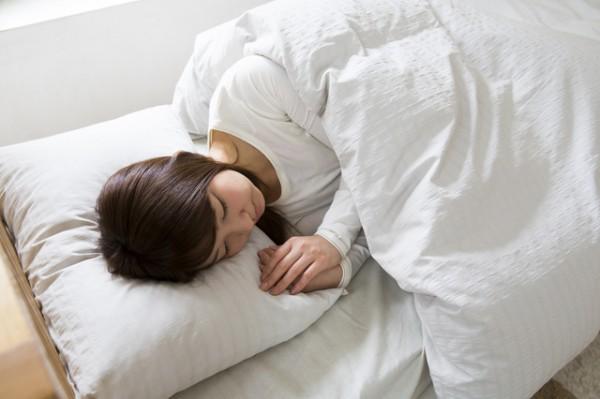 ベッドで眠っている若い女性