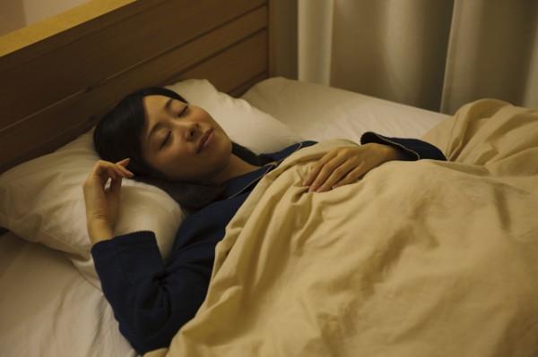 暗い寝室で眠る若い女性