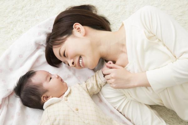赤ちゃんとお母さん布団の上で見つめあっている