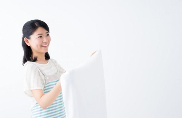 白いシーツかタオルを干してる若い女性