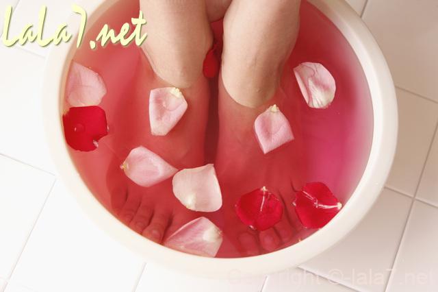 足浴 ピンク赤の湯に足首までつけている