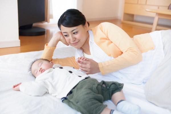 布団で眠る赤ちゃんを見つめるお母さん