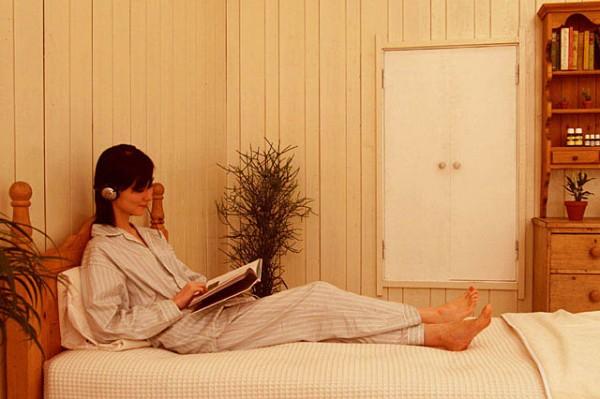 ベッドの上で本を読む女性イヤホンしている