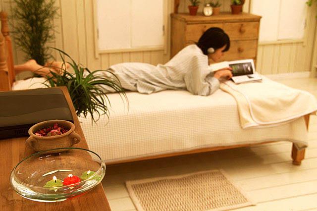 ベッドの上でうつ伏せで本を読みくつろぐ女性
