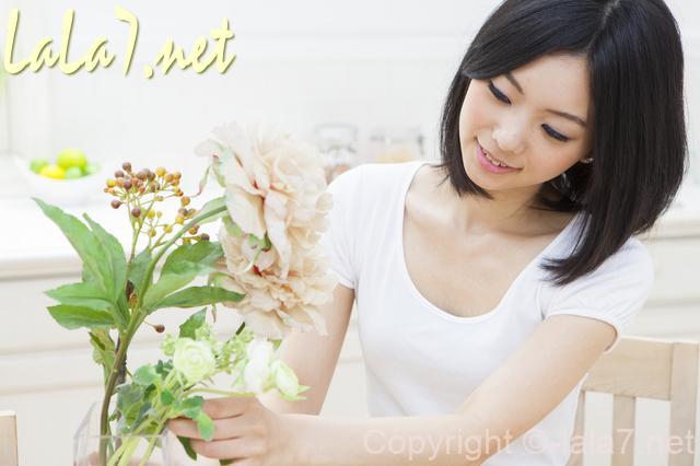 白いTシャツを着た若い女性 花瓶の花を見ている