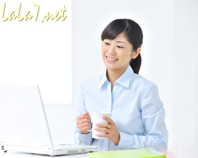 パソコンに向かう若い女性 微笑んでいる