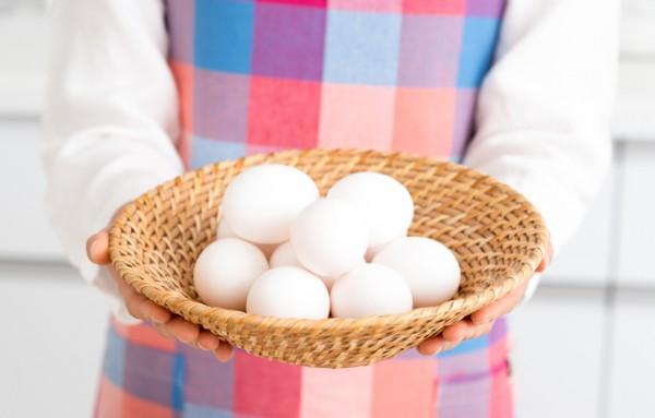 かごに入った10ほどの卵を差し出す女性