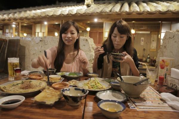 食事会飲み会女性ふたりがたくさんの料理を前にほおばる