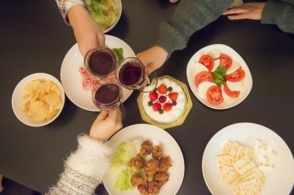 料理を囲んで赤ワインで乾杯する三人上から