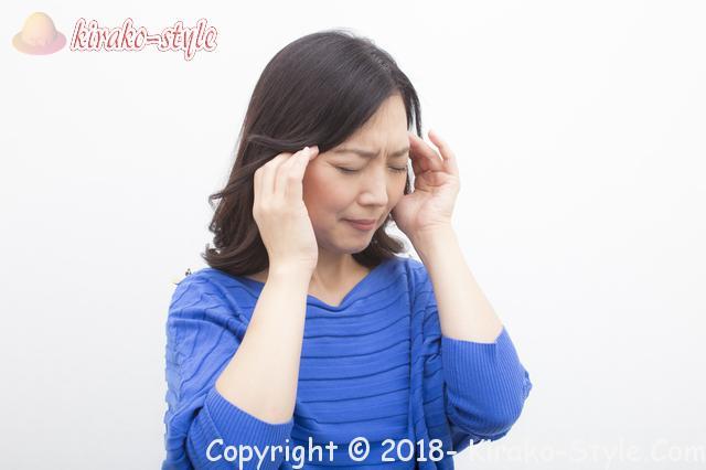 頭痛 頭に両手をやる女性
