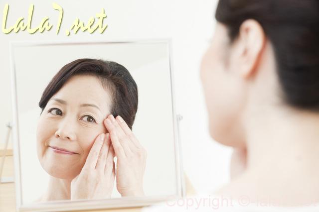 鏡に向かってお化粧中の女性