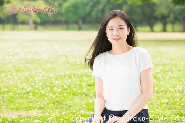 新緑の広場で若い女性一人微笑む姿