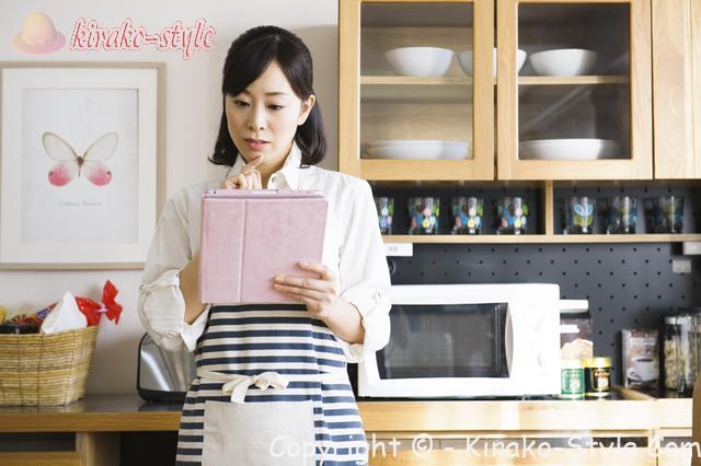 家事代行サービス、家政婦、台所でタブレットを見て悩んでいる女性