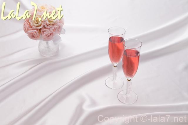 赤ワインの入ったワイングラス二つとピンクのバラのブーケ