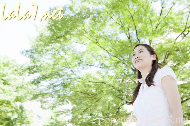 新緑の屋外 白いブラウスの女性笑顔